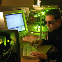 Scientist at a computer in a laser lab